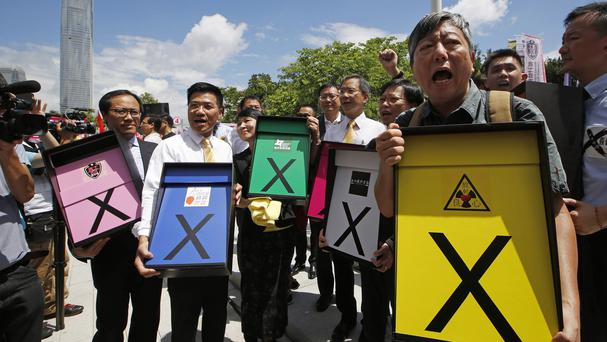 Pro-democracy MPs hold boxes of votes collected from the public against the controversial electoral proposal (AP)