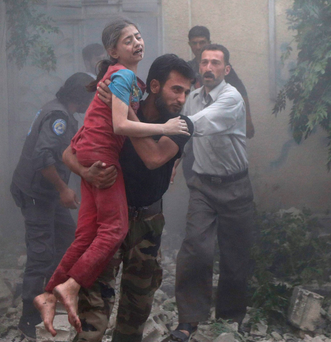 A man holds a girl who survived heavy shelling in the Douma neighbourhood of Damascus Photo: Reuters