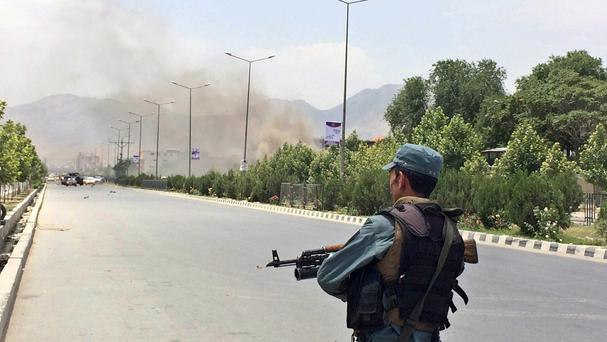 An Afghan security officer stands guard at the entry gate of the Afghan parliament after an attack by the Taliban, in Kabul (AP)