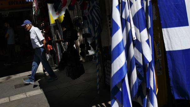 A man walks by a street shop selling Greek flags in Athens (AP)