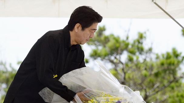 Japanese Prime Minister Shinzo Abe lays a bouquet of flowers during a memorial service at Peace Memorial Park in Itoman, on Okinawa islands (Hiroko Harima/Kyodo News via AP)