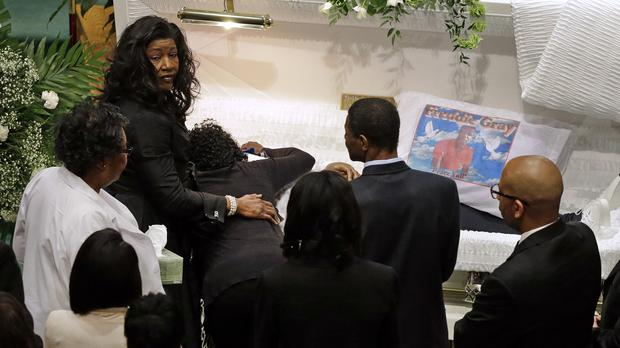 Gloria Darden, mother of Freddie Gray, is comforted as she embraces his body before his funeral in April (AP)