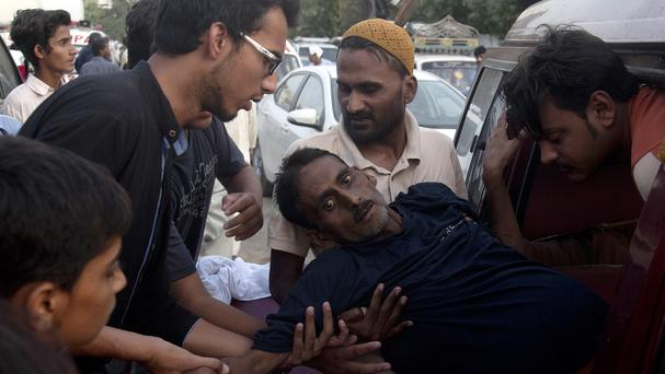 People rush a man to a hospital as he suffers from a heatstroke in Karachi. (AP)