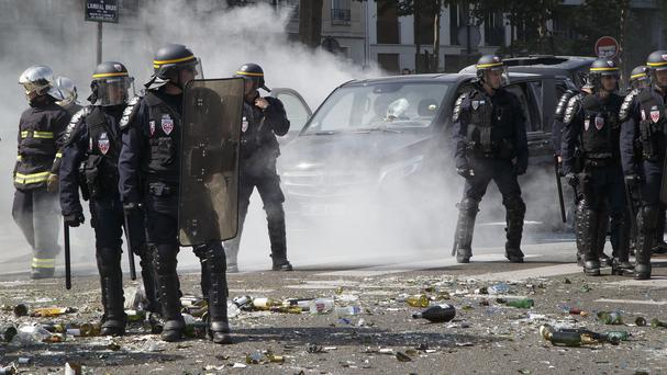 Police officers stand next to a burned out car during a taxi drivers' demonstration in Paris (AP)