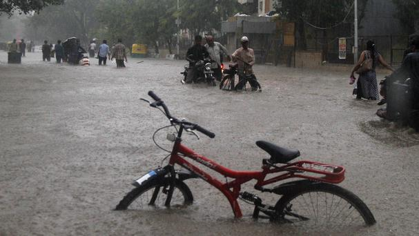 Indians wade through a flooded road during heavy monsoon rain in Ahmadabad (AP)