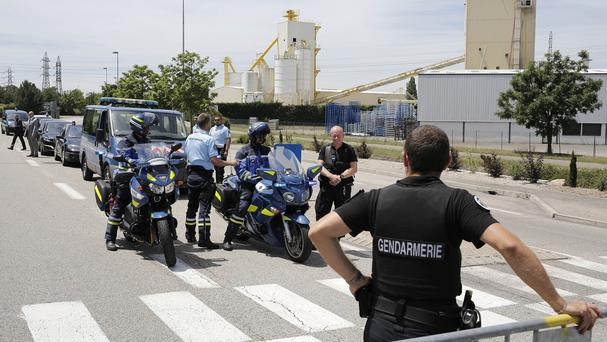 Police officers block the area where an attack took place in Saint-Quentin-Fallavier, south-east of Lyon, France (AP)