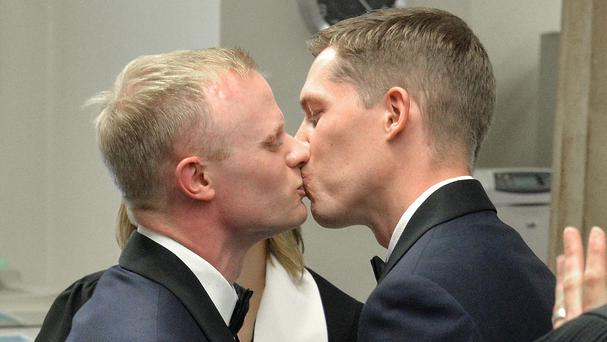 Benjamin Moore, left, and Tadd Roberts kiss after their marriage ceremony at the Jefferson County Clerks Office in Louisville, Kentucky (AP)