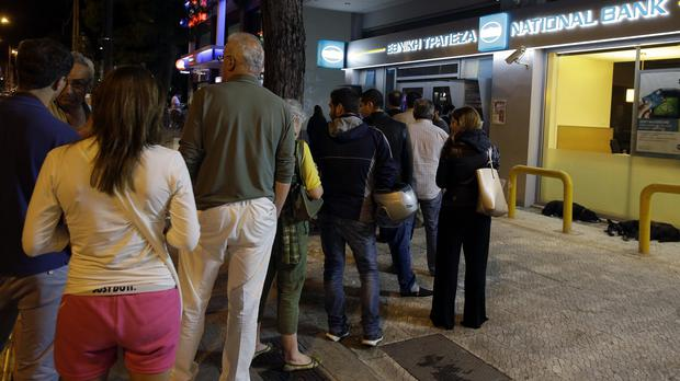 People queue to use ATMs at a bank in Athens (AP)