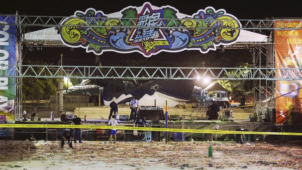 Police investigators inspect the stage area after the fire at the Formosa Water Park (AP)