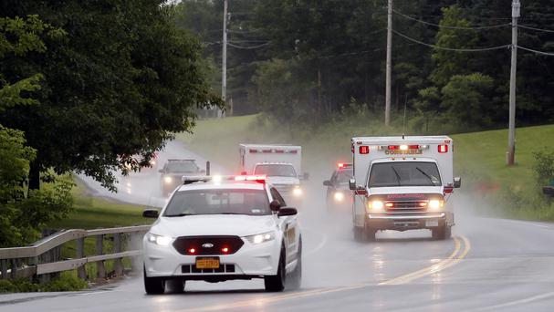Police escort ambulances from an area where law enforcement officers were searching for convicted murderer David Sweat (AP)