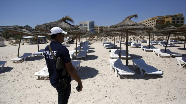 A Tunisian police officer guards a beach in front of the Imperial Marhaba Hotel in Sousse (AP)
