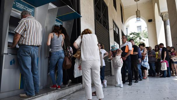 People line up at ATMs outside a National bank branch in the northern Greek port city of Thessaloniki (AP)