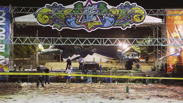 Police investigators inspect the stage area after an accidental explosion during a music concert at the Formosa Water Park in New Taipei City (AP)