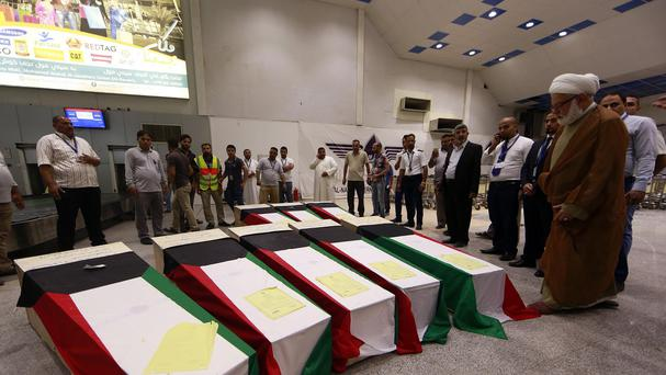 Coffins draped with Kuwaiti flags belonging to victims of a suicide bombing that targeted a Shia mosque in Kuwait arrive at Najaf Airport (AP)