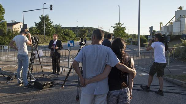 Bystanders look at the media which stand on the road leading to a plant where the attack took place in Saint-Quentin-Fallavier, south-east of Lyon (AP)