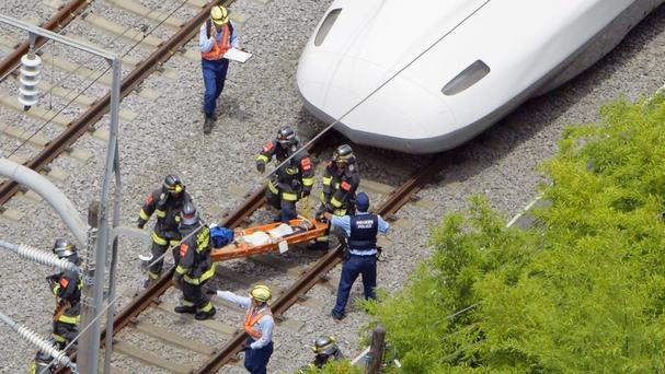 A passenger is carried out of the bullet train, which made an emergency stop in Odawara, west of Tokyo (Kyodo News/AP)