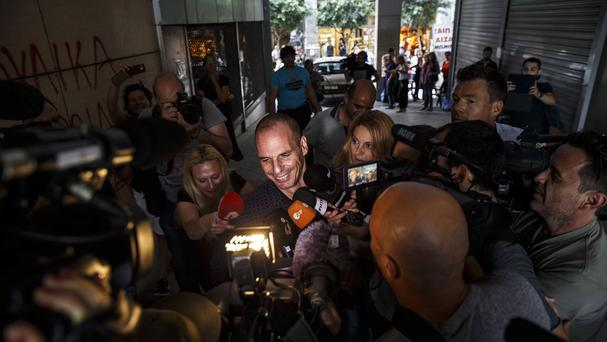 Greece's finance minister Yanis Varoufakis is surrounded by media as he leaves from his office in Athens (AP)