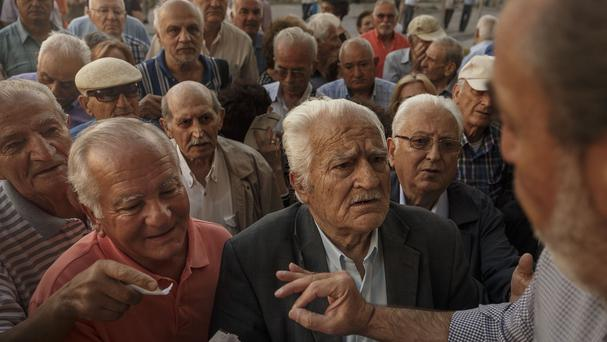 Pensioners stand in a queue outside a bank in Athens (AP)