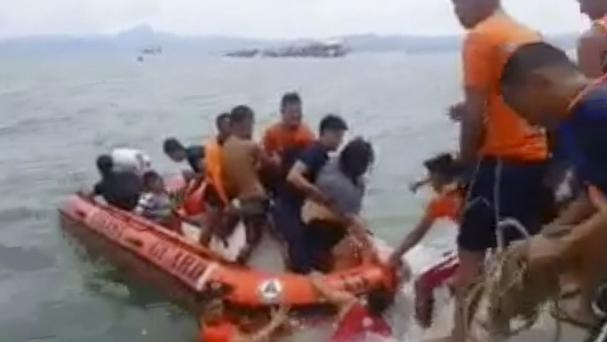 Rescuers help passengers from a capsized ferry boat in Ormoc city on Leyte Island, Philippines. (AP)