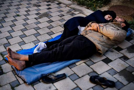 WAITING TO CROSS: A migrant couple sleep near the police station in the southern Serbian town of Presevo, near the border with Macedonia. Illegal immigrants cross Serbia on their way to other European countries as it has land access to three members of the 28-nation bloc — Romania, Hungary and Croatia. Photo: Getty