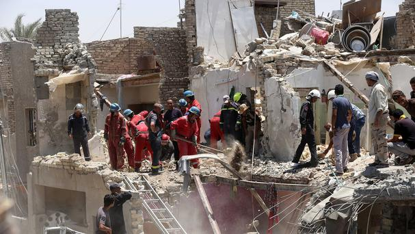Iraqi security forces search for survivors after a bombing in the eastern neighbourhood of New Baghdad (AP)