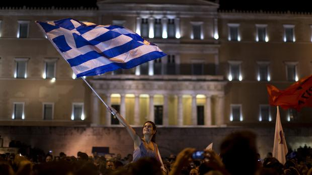A supporter of the No vote waves a Greek flag in front of parliament after the results of the referendum are revealed (AP)