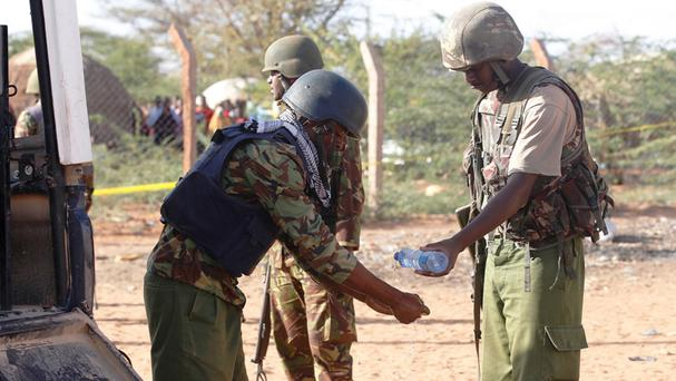 A Kenyan army officer washes his hands after carrying a dead body in Mandera (AP)