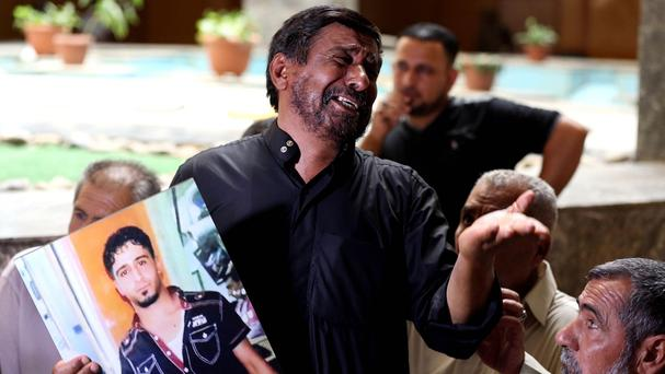 A father holds a poster of his dead son, who was an Iraqi soldier, at a courtroom in Baghdad (AP)