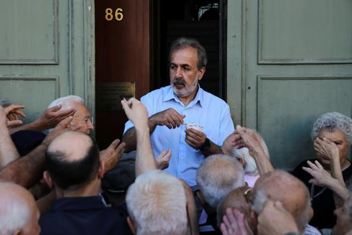 Pensioners are given priority tickets by a National Bank official, as they wait to receive part of their pensions in Athens yesterday. Photo: Reuters