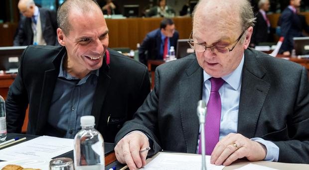 'I SHALL WEAR THEIR LOATHING WITH PRIDE': Greece's former finance minister Yanis Varoufakis tries to engage with Ireland's Michael Noonan during a meeting of EU finance ministers last February. Photo: Geert Vanden Wijngaert