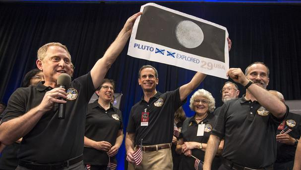 Mission team members hold a print of a US stamp with their suggested update since the New Horizons spacecraft made its closest approach to Pluto (Nasa/AP)