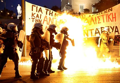 Riot police stand amongst the flames from exploded petrol bombs thrown by a small group of anti-establishment demonstrators in front of parliament in Athens yesterday. Photo: Reuters