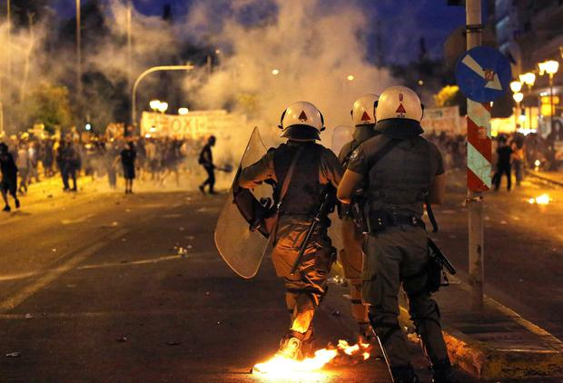 Masked anti-establishment youths and anti-austerity protesters face riot police during clashes in Athens