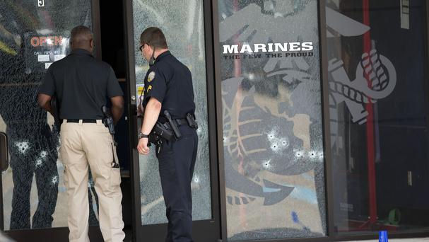 Police officers enter the Armed Forces Career Centre through a bullet-riddled door after a gunman opened fire on the building. (AP)
