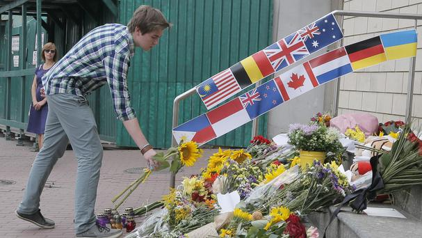 People lay flowers at the Netherlands Embassy in Kiev for Malaysia Airlines Flight MH17 crash victims. (AP)