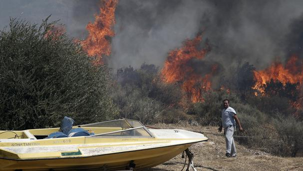 Flames burn on the mountain of Ymittos on the outskirts of Athens (AP)