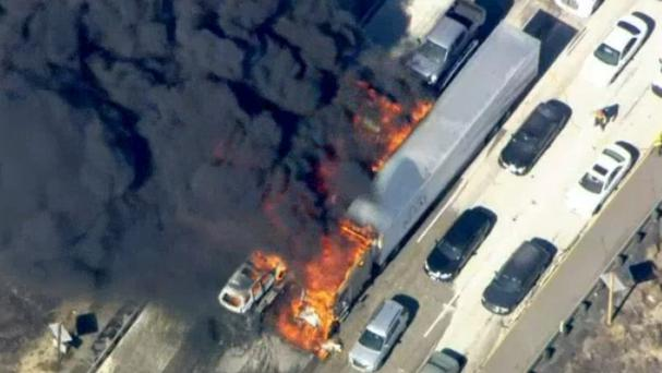 Smoke billows from vehicles as the fast-moving wildfire sweeps across a freeway near Hesperia (NBC4/AP)