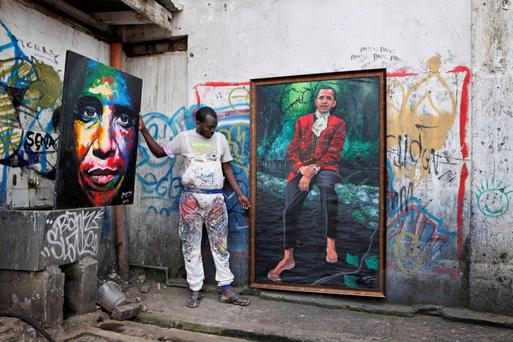 Kenyan artist Yegonizer poses next to his paintings depicting US President Barack Obama on July 15, at the Go Down Art Centre in Nairobi. Excitement is growing in Kenya ahead of US President Barack Obama's first in late July visit to his father's homeland since becoming president