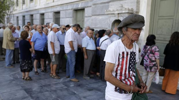 The first customers, most of them pensioners, stand in a queue to enter a bank branch in Athens as Greek banks reopen, although many restrictions on transactions, including cash withdrawals, will remain. (AP)