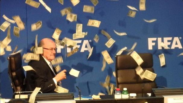 British comedian Lee Nelson (out of picture) throws cash at Sepp Blatter during an Executive Committee Meeting at Fifa headquarters, Zurich. (PA)