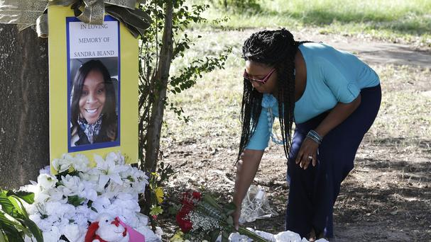 Jeanette Williams places a bouquet of roses at a memorial for Sandra Bland in Prairie View, Texas (AP)