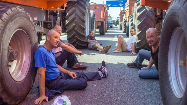 Farmers use their tractors to block the main Paris to Lyon road in France (AP)