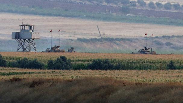 Turkish army tanks hold positions near the border with Syria, in the outskirts of the village of Elbeyi (AP)