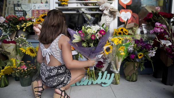 A young girl leaves flowers at a memorial to victim Jillian Johnson following the deadly shooting at a Louisiana cinema (AP)