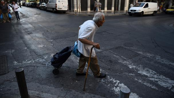An elderly man pulls his shopping cart in Athens as it was confirmed talks on a third bailout for Greece are facing delays (AP)