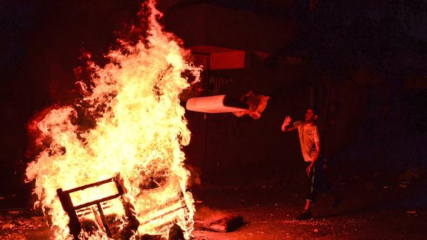 A left-wing protester throws wood into a fire lit by demonstrators, to help avoid tear gas used by police to disperse them, in Istanbul (AP)