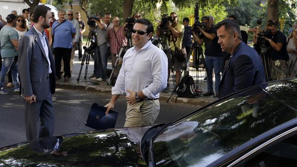 Greek Prime Minister Alexis Tsipras (centre) arrives at Syriza party HQ for a meeting with senior party officials in Athens (AP)