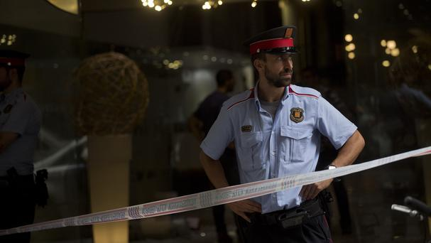 A police officer stands guard at the entrance of a hotel following a shooting in Barcelona (AP)