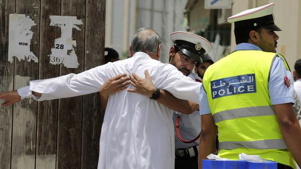 Worshippers are searched outside a Shiite Muslim mosque after a bombing in Bahrain which killed two police officers (AP)