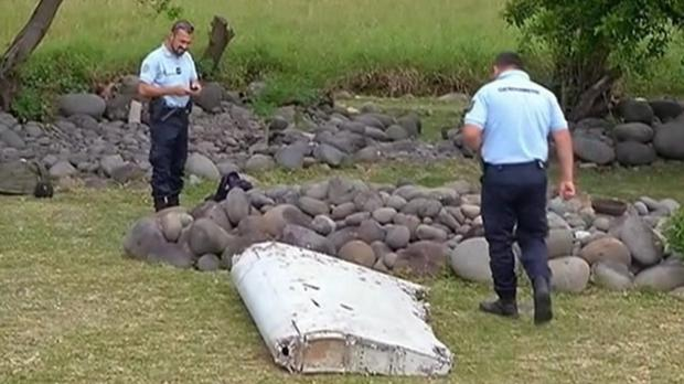Police officers look over a piece of debris that washed up on the French island of Reunion Credit: Reunion 1ere/AP